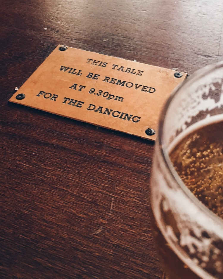 A table at Hootenanny's with a plaque in the centre saying 'This table will be removed at 9.30pm for the dancing'