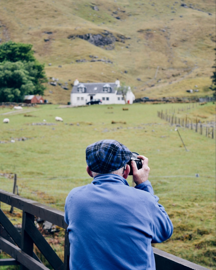 A man in a tartan cap takes a photo of an iconic white cottage in Glen Coe