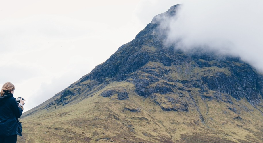 A woman stands with her camera pointing towards a cloud-shrouded mountain in Glen Coe, Scotland