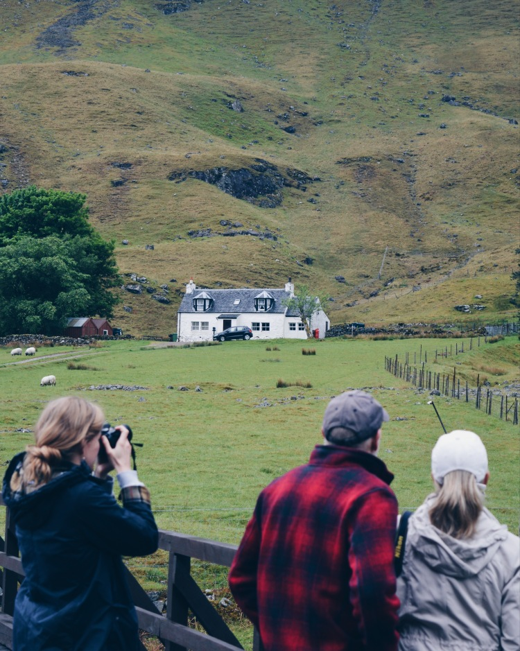 A group of people take photos of a white house in Glen Coe