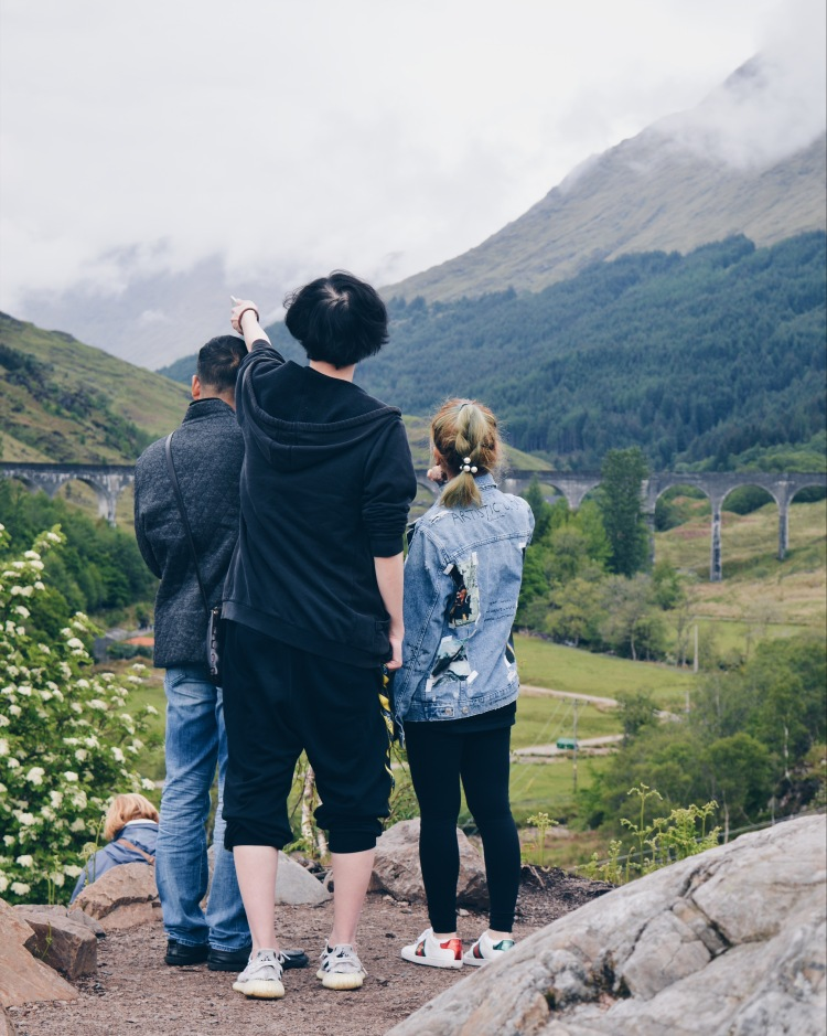 A group of people point at Glenfinnan Viaduct