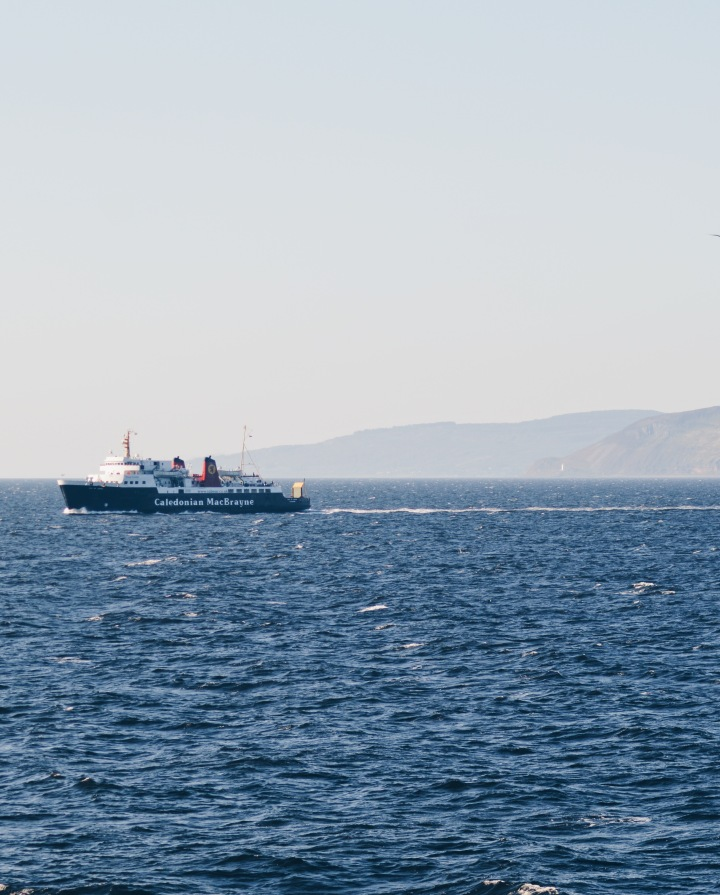 A Caledonian MacBrayne ferry with a hazy Isle of Arran behind it
